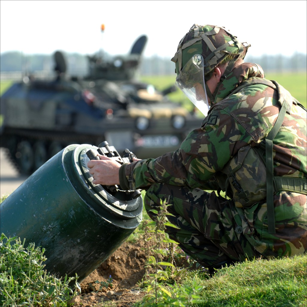 A Royal Air Force bomb disposal expert carefully attaches a Rocket Wrench to the tail of a 1000lb bomb during a training exercise at RAF Wittering, Cambridgeshire. A CVR(T) Spartan Armoured Vehicle waits in the background.  The Rocket Wrench is a robust high torque wrench, developed for the MoD as a means of unscrewing fuses from explosive devices at a safe distance. It is designed to be used by EOD/IED Bomb Technicians and by Military Bomb Squad personnel, to assist in the defusing of unexploded bombs, grenades and other unscrew type explosive devices such as fire extinguishers or household gas cylinders that have been converted into IEDs.